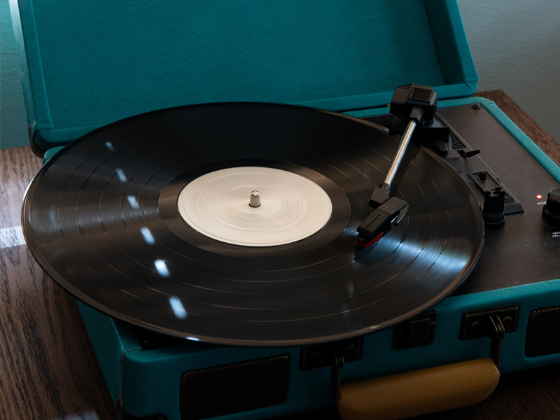 A record player, open and playing vinyl